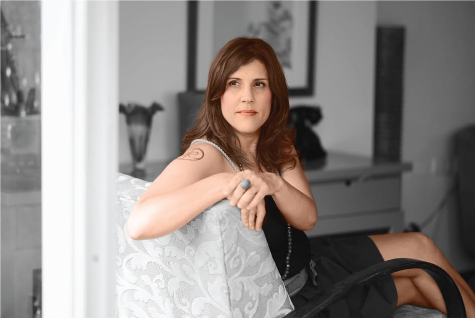 שרון אלה מעצבת פנים מומחית לחומרים, יושבת על כורסה בסלון ביתה ומביטה למצלמה