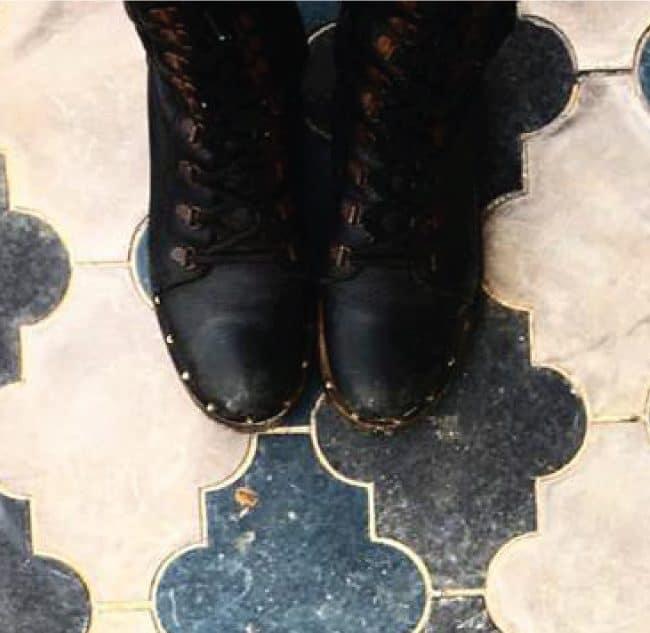מגפיים שחורות שנועלת שרון אלה על רקע אריחי בטון בצורת תלתן ממרוקו