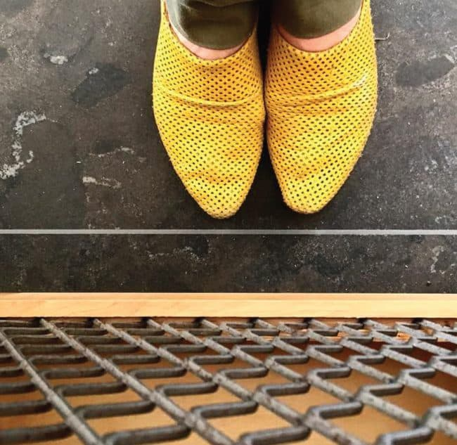 שרון אלה נועלת כפכפים צהובות ועומדת על רצפת אבן אפורה כהה מסוג בלו -סטון , למול חזית דלת מטבח מעץ אלון מלא בשילוב רשת ברזל מתועשת
