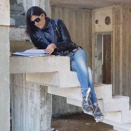 שרון אלה מעצבת פנים, בעת פיקוח שטח בתהליך בניה בקיבוץ געש, יושבת על מדרגות הבטון היצוק