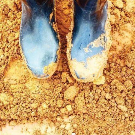 שרון אלה נועלת מגפי גומי בעת פיקוח שטח על מצע חול.