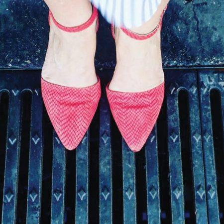 שרון אלה נועלת סנדלים אדומות על רקע רצפת רחוב עם כיסויי ברזל לניקוזי מים