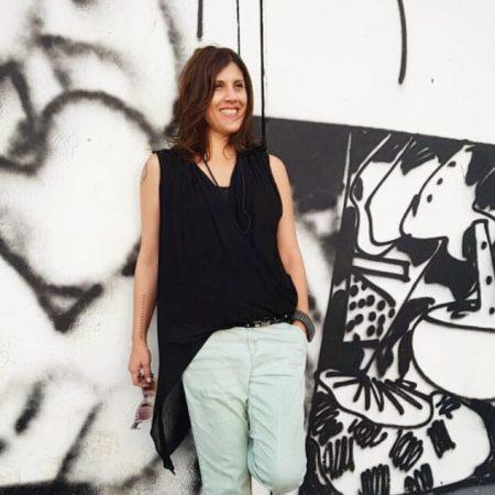 שרון אלה על רקע קיר גרפיטי בסיור בעיר התחתית בחיפה