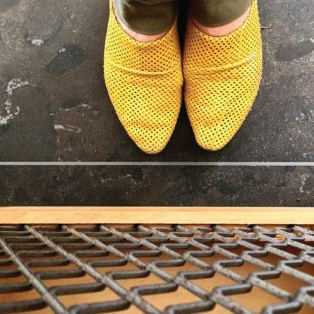 כפכפים צהובות על רקע רצפת אבן בלו סטון ויחידת נגרות בשילוב עץ מלא ורשת מתועשת