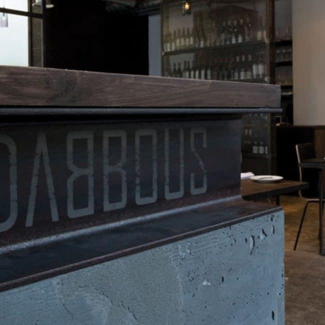 פרט חיבור בקיר דלפק המורכב מקיר בטון ורלס קורת ברזל חשופה המתחברים לדלפק עץ מלא במסעדה בלונדון