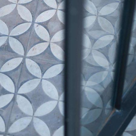 רצפת אריחי בטון מוטבעים בגוונים של אפור, בחצר מרוצפת בבית פרטי בהרצליה
