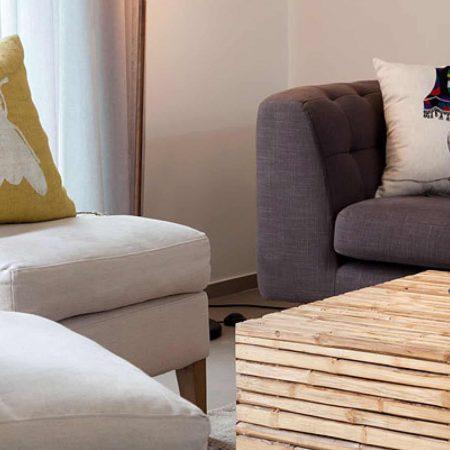 סלון בדירת גג תל אביבית. שולחן עשוי במבוק ,שטיח טלאים בגוון אפור, כורסאות מרופדות בבד פשתן בגוון טבעי