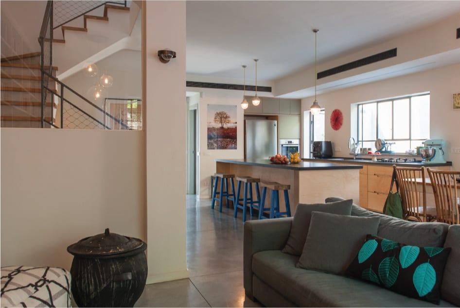 בית פרטי בהרצליה עם רצפת בטון אפור מוחלק ,מבט מהסלון לכיוון המטבח והכניסה לבית