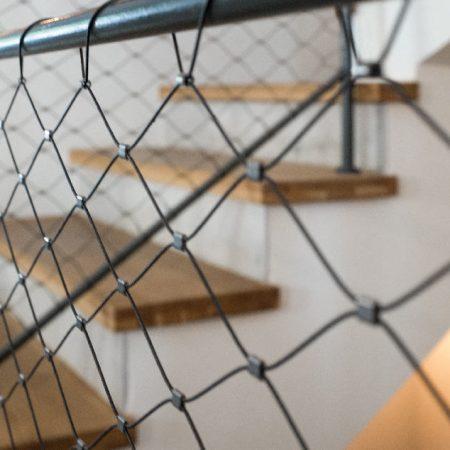 פרט מגרם מדרגות של 4 קומות בבית פרטי בהרצליה. חיפוי שלחי מדרגות בעץ אלון מלא. מעקה עשוי מסגרות ברזל עם רשת אקסטנדד מנירוסטה
