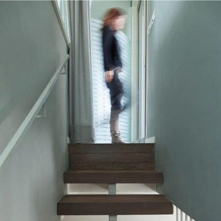מבט מהמדרגות עם מעקה רשת אקסטנדד מנירוסטה לכיוון קומת הכניסה המטבח והסלון בבית בהרצליה