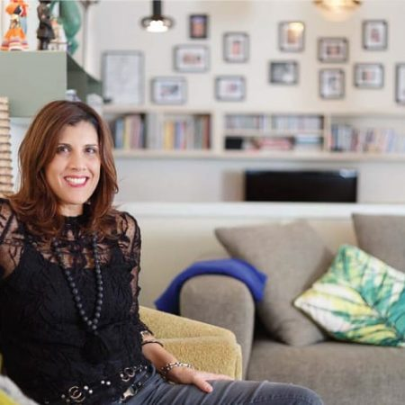 שרון אלה יושבת על הספה בסלון ביתה בדירתה בנוף ים