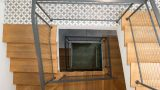 גרם מדרגות של 4 קומות בבית פרטי בהרצליה. חיפוי שלחי מדרגות בעץ אלון מלא. מעקה עשוי מסגרות ברזל עם רשת אקסטנדד מנירוסטה