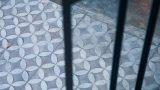 אריחי בטון מוטבעים בגוונים של אפור ולבן ברצפת חצר בבית בהרצליה