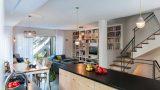 יחידת אי במטבח עשויה סנדוויץ ליבנה חשוף ומשטח עץ אלון שחור . מבט לכיוון הסלון והיציאה לגינה בבית פרטי בהרצליה