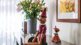 שידת סלון ועליה פסלונים של בובת פינוקיו מעץ , ובובה אפריקאית בדירת גן בנוף ים