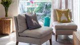 שולחן סלון מבמבוק על גבי שטיח טלאים ולצד כורסאות בבד פשתן , בסלון דירת גג בתל אביב . מבט לכיוון המרפסת